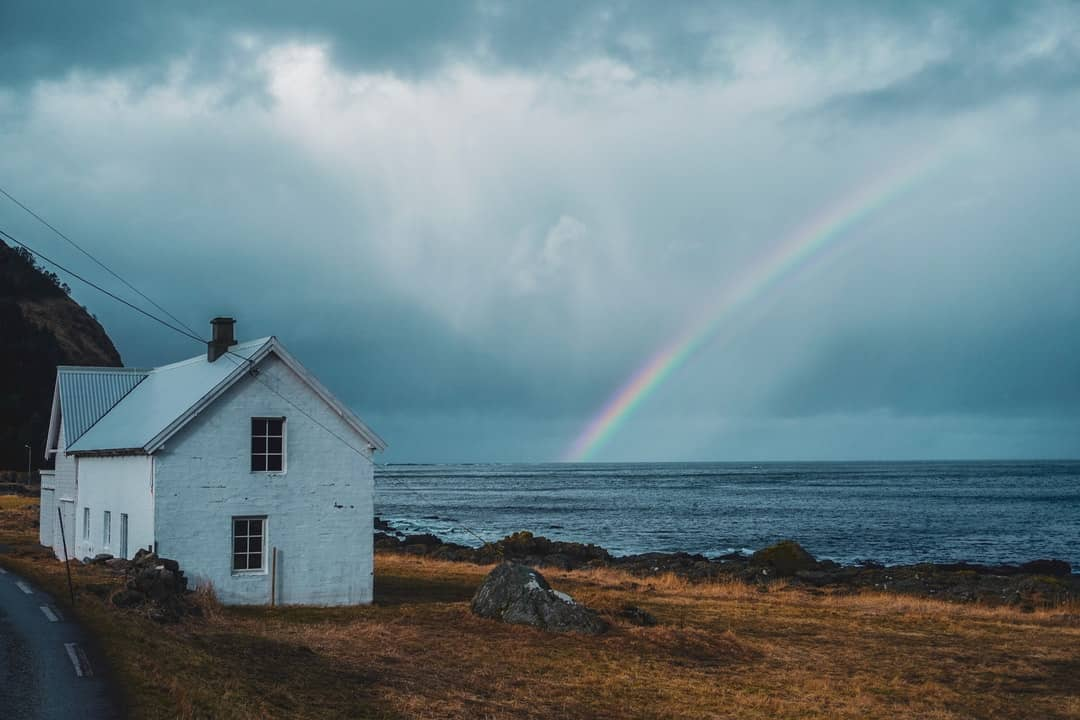 A rainbow in front of a house